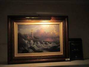 "THOMAS KINKADE CONQUERING THE STORMS SEA SIDE MEMORIES VI. LIMITED EDITION LITHOGRAPH WAS ADDITIONALLY HIGH-LIGHTED BY A THOMAS KINKADE MASTER APPRENTICE. INCLUDES COA AND ORIGINAL RECIEPT. MEASURES 28"" X 22"""